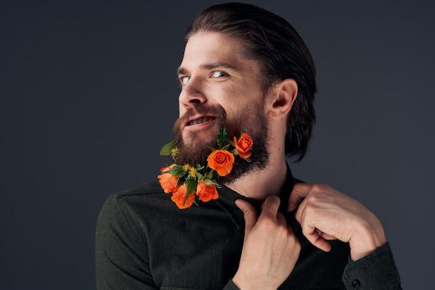 Bärtiger fröhlicher mann blüht verschiedene romantikdekoration schwarzen hintergrund Premium Fotos