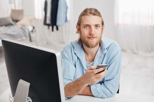 Bärtiger, gut aussehender männlicher büroangestellter mit sanftem lächeln liest die benachrichtigung auf dem smartphone, sitzt mit dem handy vor dem bildschirm im coworking space, sendet feedback an mitarbeiter und surft im internet Kostenlose Fotos