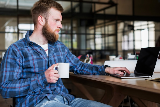 Bärtiger junger geschäftsmann, der an laptop mit dem halten der kaffeetasse arbeitet Kostenlose Fotos