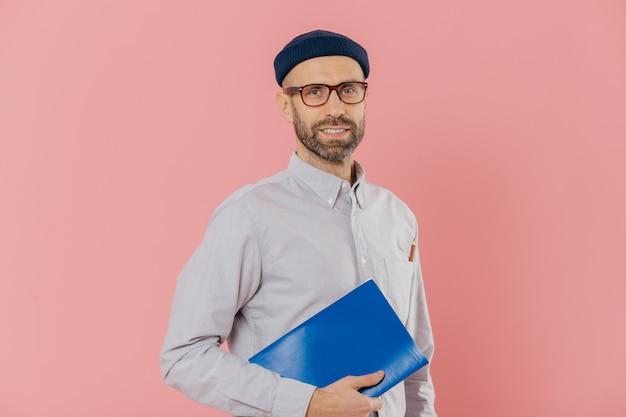 Bärtiger junger kaukasischer mannstudent hält lehrbuch, bereitet sich für abschlussprüfung vor, trägt gläser Premium Fotos