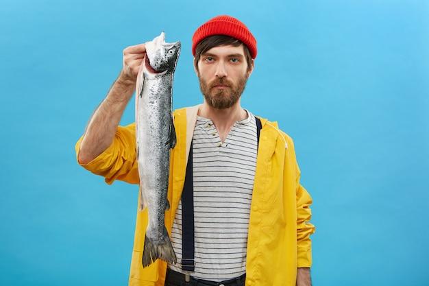 Bärtiger junger mann, der großen fisch im teich angelt und damit über der blauen wand posiert, die ernsten ausdruck hat. erfolgreicher fischer, der langen großen lachs in händen hält und seinen riesigen fang demonstriert Kostenlose Fotos