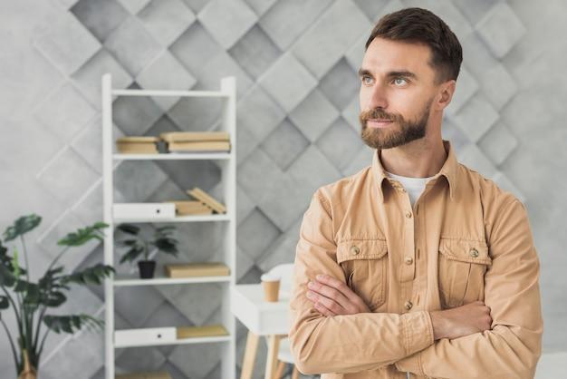 Bärtiger junger mann, der in einem büromittelschuß steht Kostenlose Fotos