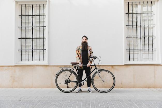 Bärtiger junger mann, der mit fahrrad gegen wand steht Kostenlose Fotos