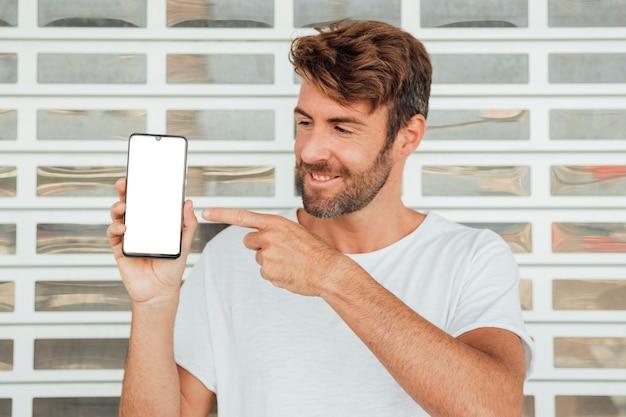 Bärtiger junger mann, der smartphone zeigt Kostenlose Fotos
