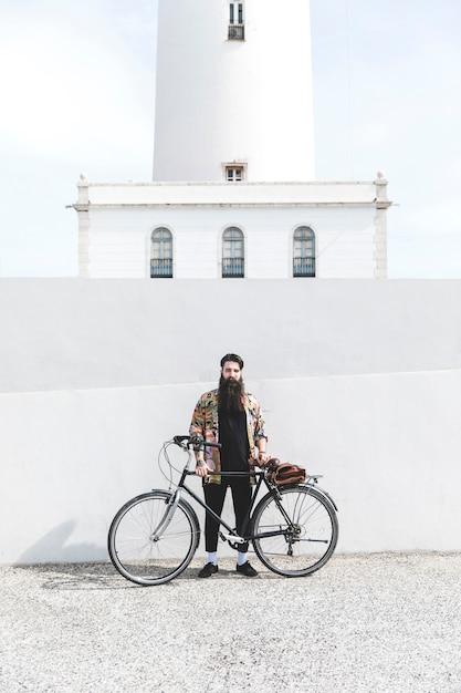Bärtiger junger mann, der vor leuchtturm steht Kostenlose Fotos