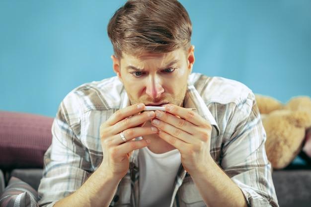 Bärtiger kranker mann mit kamin, der zu hause auf sofa sitzt und körpertemperatur misst. Kostenlose Fotos
