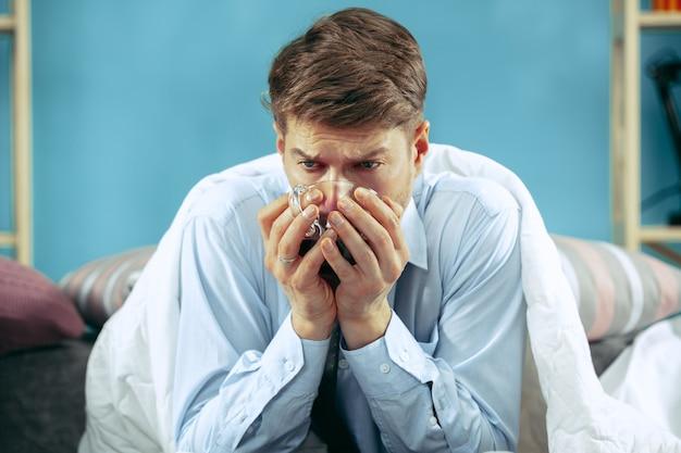 Bärtiger kranker mann mit kamin, der zu hause auf sofa sitzt und tee trinkt. Kostenlose Fotos