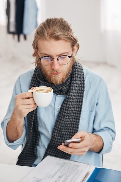 Bärtiger männlicher büroangestellter in runden brillen, gekleidet in blaues hemd und schal, umgeben von papieren und dokumenten, erhält geschäftsnachricht auf smartphone, typen antwort, trinkt kaffee. Kostenlose Fotos