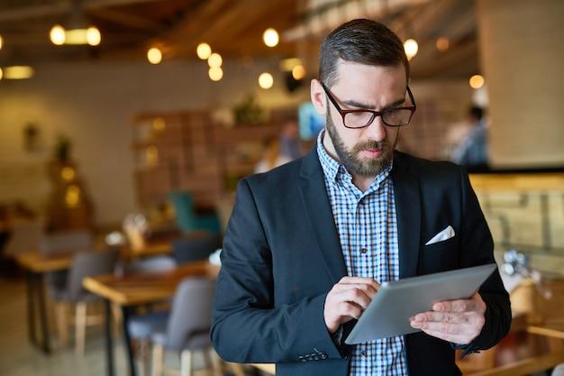 Bärtiger manager using digital tablet Kostenlose Fotos