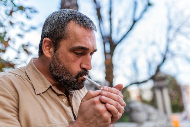 Bärtiger mann, der auf der straße raucht Premium Fotos