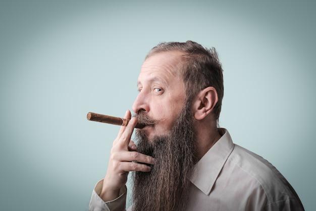Bärtiger mann, der eine zigarre raucht Premium Fotos