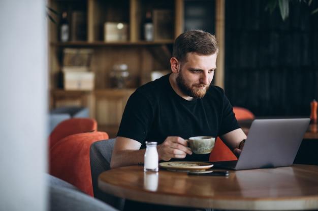 Bärtiger mann, der in einem trinkenden kaffee des cafés sitzt und an einem computer arbeitet Kostenlose Fotos