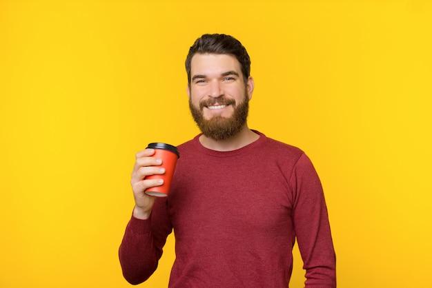 Bärtiger mann, der lächelt und eine tasse heißes getränk auf gelbem hintergrund hält. Premium Fotos