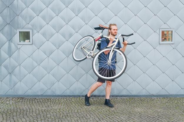 Bärtiger mann, der sein fahrrad an draußen trägt Kostenlose Fotos