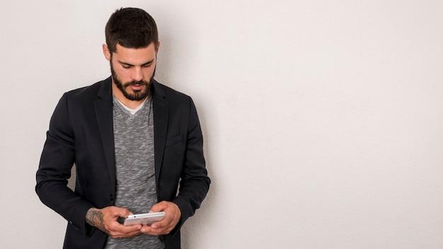 Bärtiger mann, der smartphone auf weißem hintergrund verwendet Kostenlose Fotos