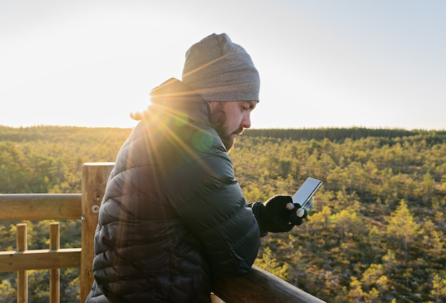 Bärtiger mann, der smartphone gegen wald betrachtet Premium Fotos