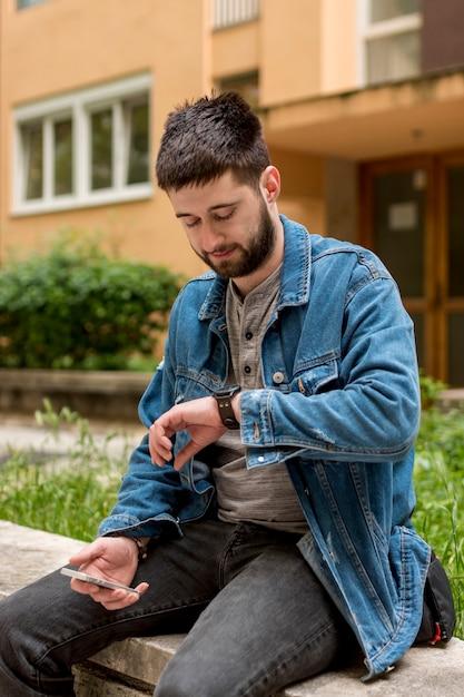 Bärtiger mann, der uhren beim halten des smartphone betrachtet Kostenlose Fotos