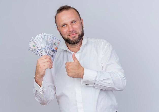 Bärtiger mann, der weißes hemd hält, das lächelnd bargeld
