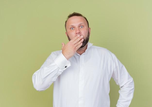 Bärtiger mann, der weißes hemd trägt, das mund mit hand bedeckt, die über heller wand schockiert steht Kostenlose Fotos