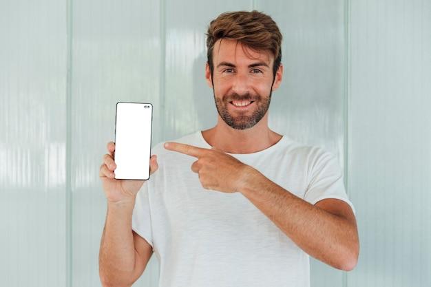 Bärtiger mann des smiley, der mobiltelefon zeigt Kostenlose Fotos