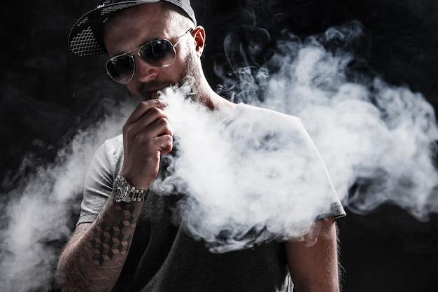 Bärtiger mann gekleidet in einem grauen hemd, in einer sonnenbrille und in einem baseballmützendampfen Premium Fotos