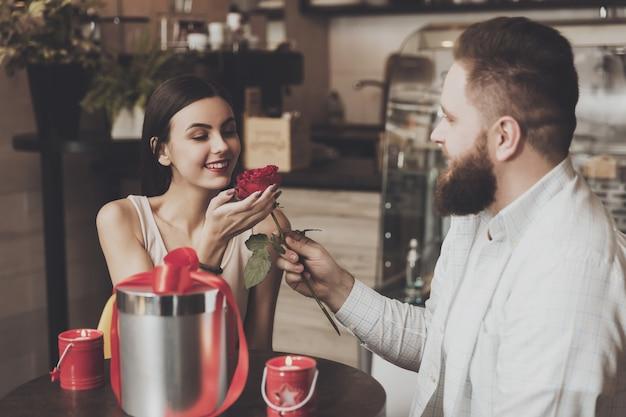 Bärtiger mann gibt dem schönen lächelnden mädchen eine rose Premium Fotos