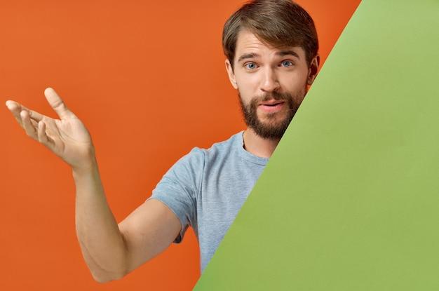Bärtiger mann im grauen t-shirt hinter einem grünen plakat auf orange wand. Premium Fotos