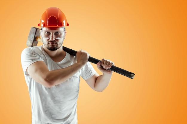Bärtiger mann in einem sturzhelm hält einen vorschlaghammer auf einem orangefarbenen hintergrund Premium Fotos