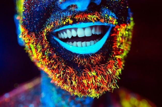 Bärtiger mann in fluoreszierendem puder gemalt Premium Fotos