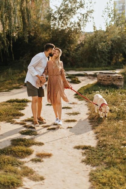 Bärtiger mann küsst seine freundin auf die wange und hält ihre hand. paar, das mit labrador im garten geht. Kostenlose Fotos
