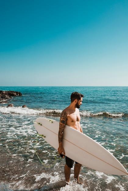 Bärtiger mann mit dem surfbrett, das wellenartig bewegendes meer betrachtet Kostenlose Fotos