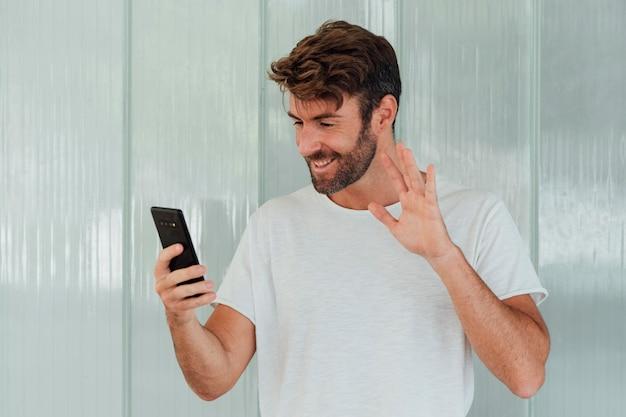 Bärtiger mann mit dem telefon, das an der kamera aufgibt Kostenlose Fotos