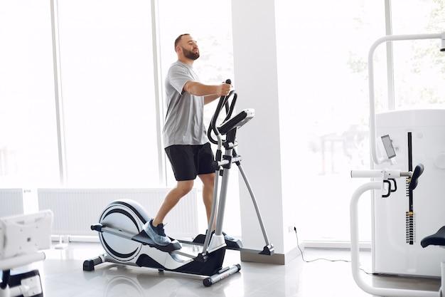 Bärtiger mann mit spinbike im physiotherapieraum Kostenlose Fotos