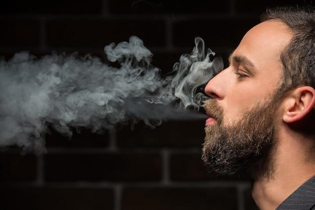Bärtiger mann raucht gegen backsteinmauer. Premium Fotos