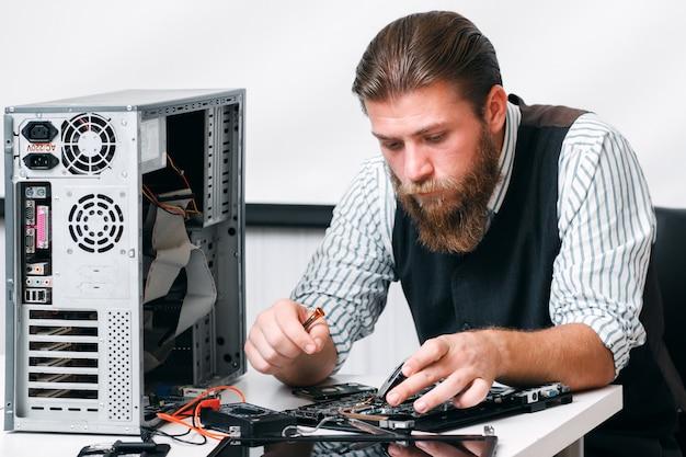 Bärtiger mechaniker repariert computerschaltung. programmiererdiagnose innerhalb eines teils der cpu. elektronische reparatur, renovierungskonzept Premium Fotos
