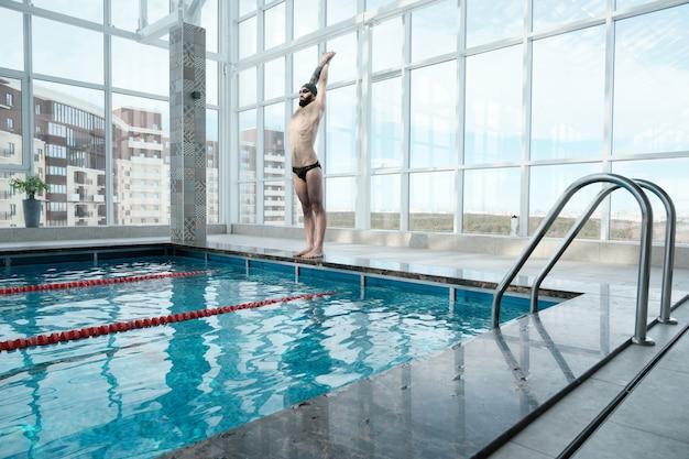 Bärtiger schwimmer mit muskulösem körper, der am rand des pools steht und körper vor dem schwimmen streckt Premium Fotos