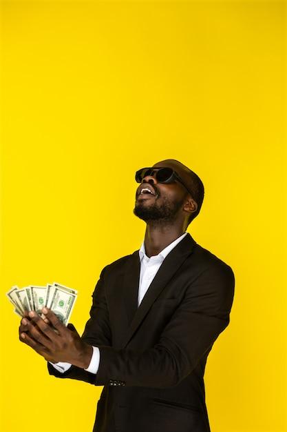 Bärtiger stilvoller junger afroamerikanischer kerl hält dollar in beiden händen und wird sie oben werfen, sonnenbrille und schwarzen anzug tragend Kostenlose Fotos