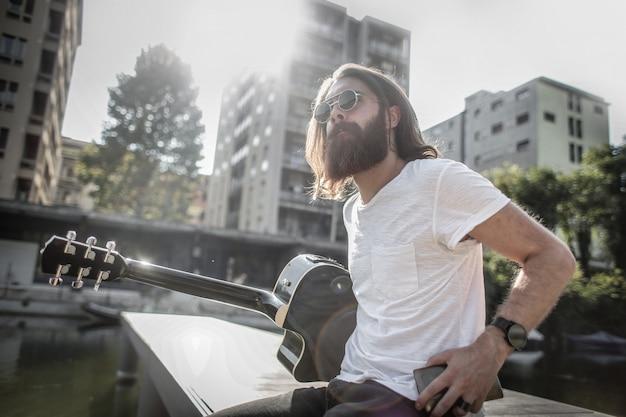 Bärtiger stilvoller mann mit einer gitarre Premium Fotos