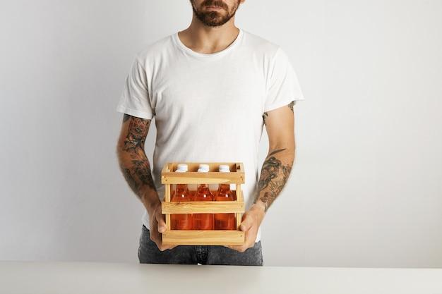 Bärtiger und tätowierter mann, der eine kleine kiste mit sechs nicht gekennzeichneten glasflaschen des handwerklichen lagerbiergetränks auf weißer wand hält Kostenlose Fotos