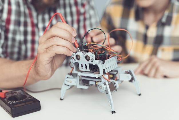 Bärtiger vater und sohn, die zu hause roboter konstruiert. Premium Fotos