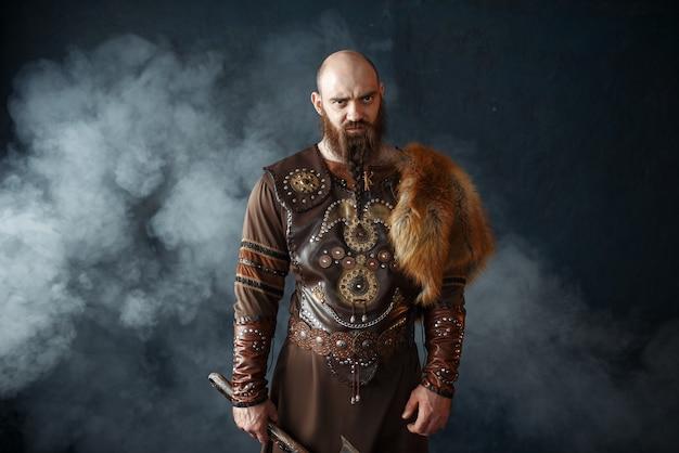 Bärtiger wikinger mit axt in traditioneller nordischer kleidung Premium Fotos