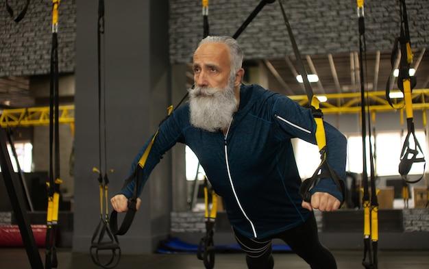 Bärtiges senior-sportler-training mit trx-widerstandsbändern im fitnessstudio. Premium Fotos