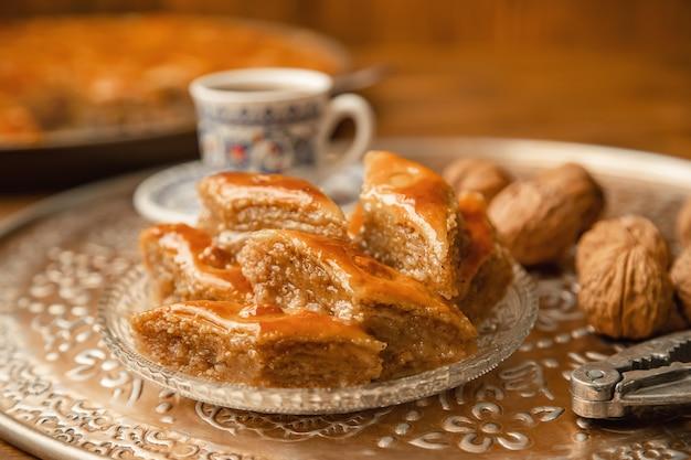 Baklava mit nüssen auf einem hölzernen hintergrund. tiefenschärfe. Premium Fotos