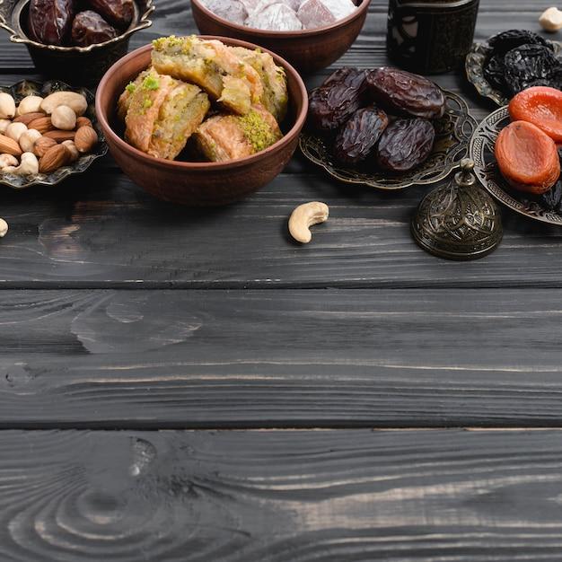 Baklava-süßigkeiten der türkischen freude; trockenfrüchte und nüsse auf schreibtisch aus holz Kostenlose Fotos