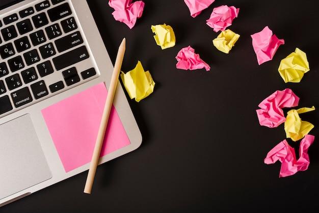 Ball von zerknitterten papieren mit anhaftender anmerkung und bleistift auf laptop gegen schwarzen hintergrund Kostenlose Fotos