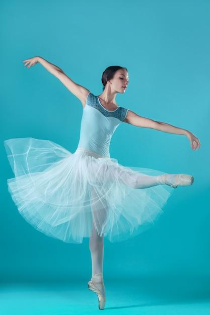 Ballerina im weißen kleid, das auf zehen aufwirft Kostenlose Fotos