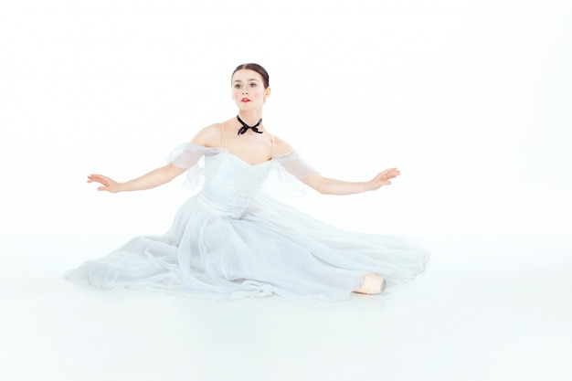 Ballerina im weißen kleid sitzen, studio. Kostenlose Fotos