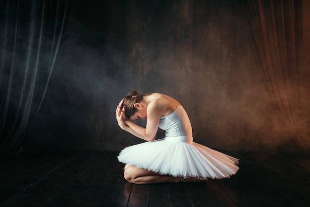 Ballerina im weißen kleid sitzt auf theaterbühne, seitenansicht. klassische balletttänzerausbildung in der klasse auf schwarz Premium Fotos