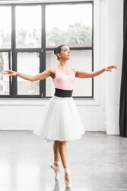 Ballerina-tänzer, der auf tippzehe im tanzboden tanzt Kostenlose Fotos