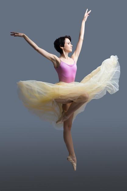 Ballerina tanzt auf einem grau Premium Fotos